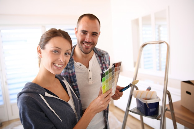 Casal na nova casa, escolhendo a cor para paredes