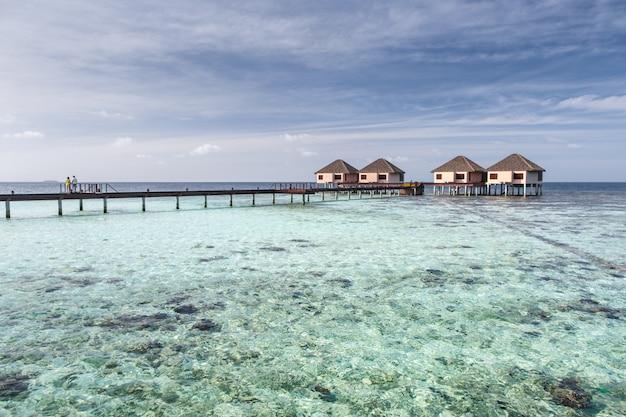 Casal na ponte de água villas em águas cristalinas na ilha tropical
