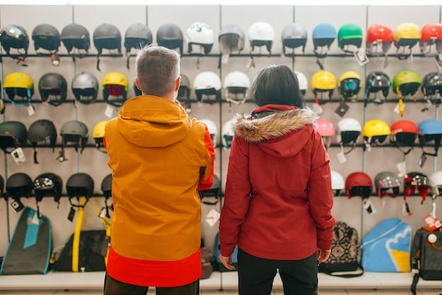 Casal na vitrine escolhendo capacetes para esqui ou snowboard