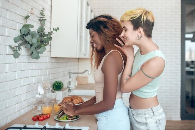 Casal, namoradas. jovem adulta americana feliz cozinhando café da manhã e namorada caucasiana em pé atrás olhando comovente