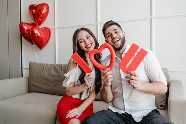 Casal namorado e namorada com vermelho eu te amo letras e balões em forma de coração em casa no sofá