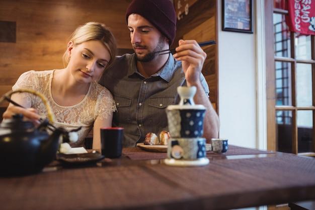 Casal namorando enquanto come sushi