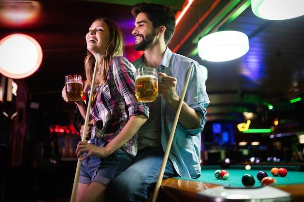 Casal namorando, flertando e jogando bilhar em um salão de sinuca