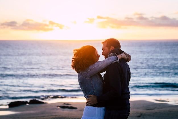 Casal namorando romântico no romance abraço relacionamento com praia e pôr do sol em abckground - conceito de pessoas juntas para sempre - mulher beija homem ao ar livre durante as férias