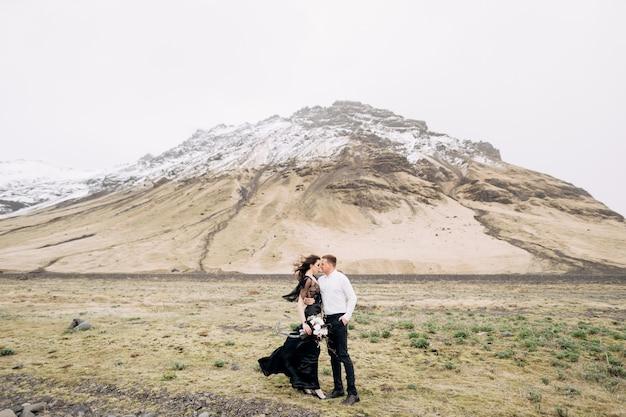 Casal nas montanhas nevadas, mulher de vestido preto e homem se abraçando