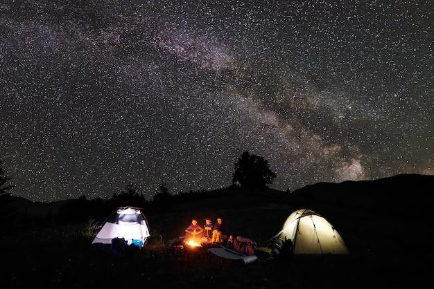 Casal nas montanhas por fogo sob o céu estrelado