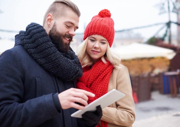 Casal navegando em tablet digital no inverno