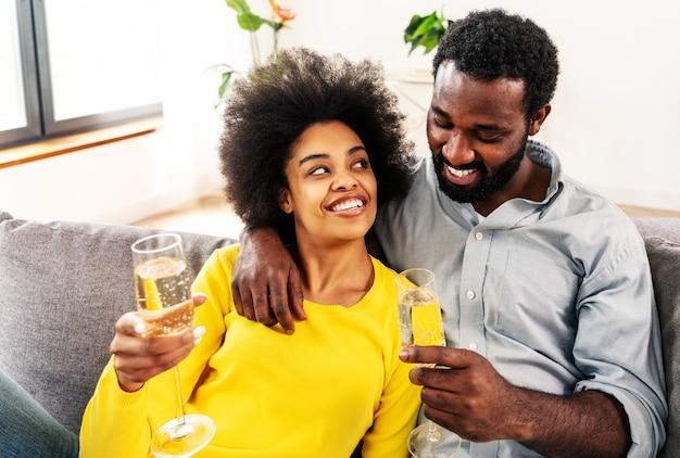 Casal negro bebendo vinho espumante em casa para comemorar - casal alegre se unindo e tomando um aperitivo