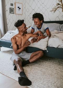 Casal negro feliz conversando na cama enquanto bebe café