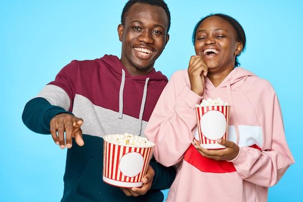 Casal negro rindo e comendo pipoca enquanto assiste a um filme