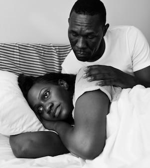 Casal negro tendo uma briga, o homem tenta pedir desculpas, mas a mulher não fala