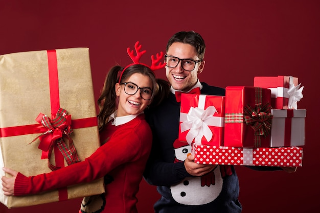 Casal nerd feliz segurando muitos presentes de natal