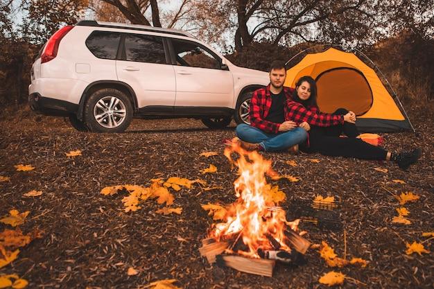 Casal no acampamento sentado perto da barraca da fogueira e o carro no fundo