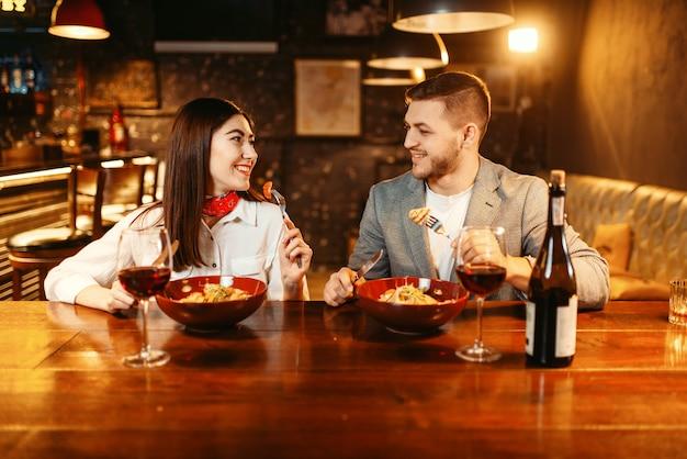 Casal no balcão do bar de madeira, jantar romântico com vinho tinto.