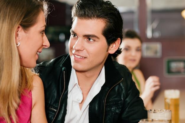 Casal no bar bebendo cerveja flertando