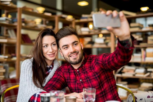 Casal no café bar, tirando uma foto.