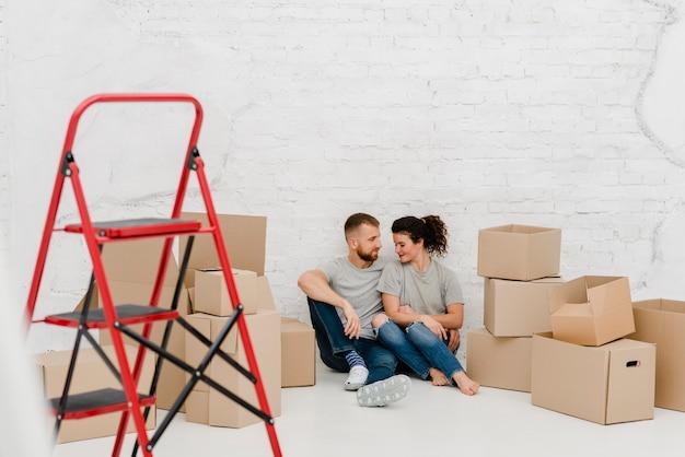 Casal no chão em apartamento novo
