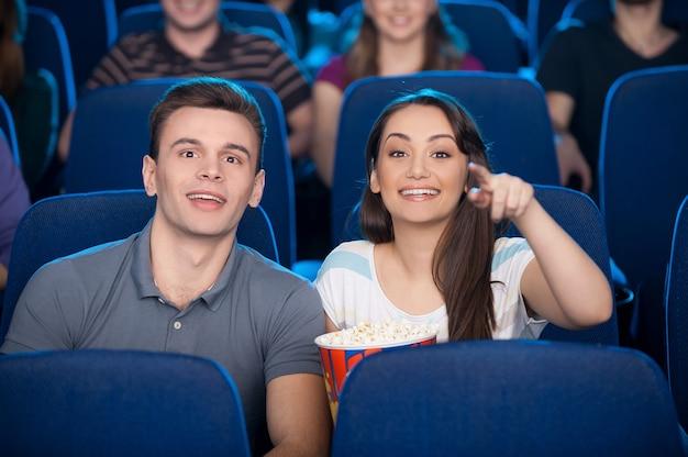 Casal no cinema. jovem casal feliz comendo pipoca e bebendo refrigerante enquanto assiste a um filme no cinema