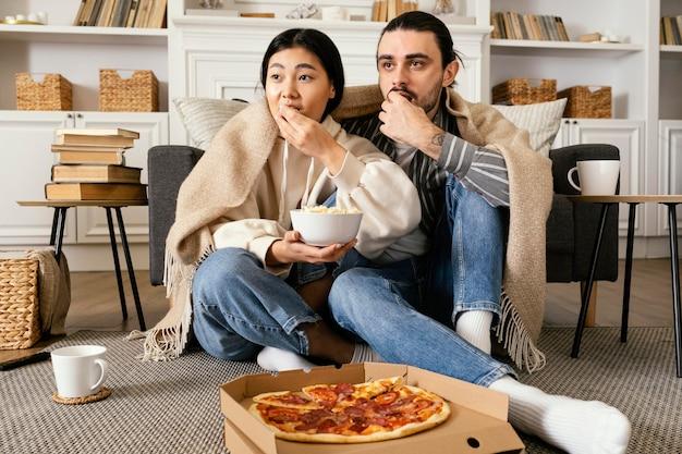 Casal no cobertor comendo pizza e pipoca