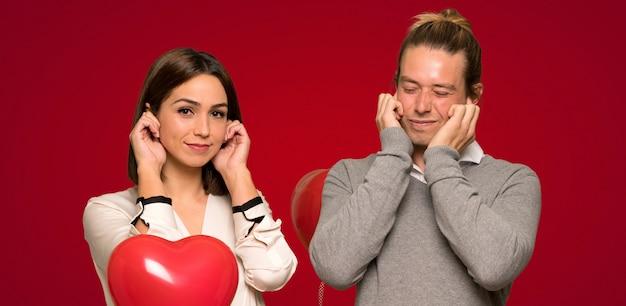 Casal no dia dos namorados, cobrindo as orelhas com as mãos. expressão frustrada sobre fundo vermelho