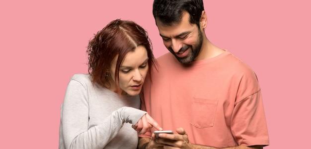 Casal no dia dos namorados, enviando uma mensagem com o celular sobre fundo rosa isolado