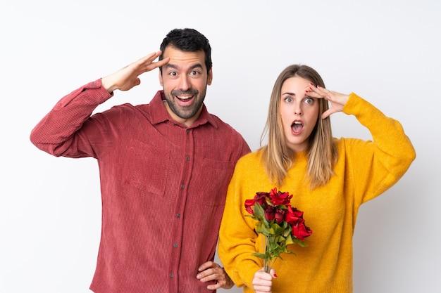 Casal no dia dos namorados segurando flores sobre parede isolada acaba de perceber algo e pretende a solução