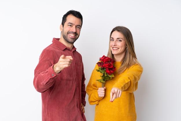Casal no dia dos namorados, segurando flores sobre parede isolada aponta o dedo para você com uma expressão confiante