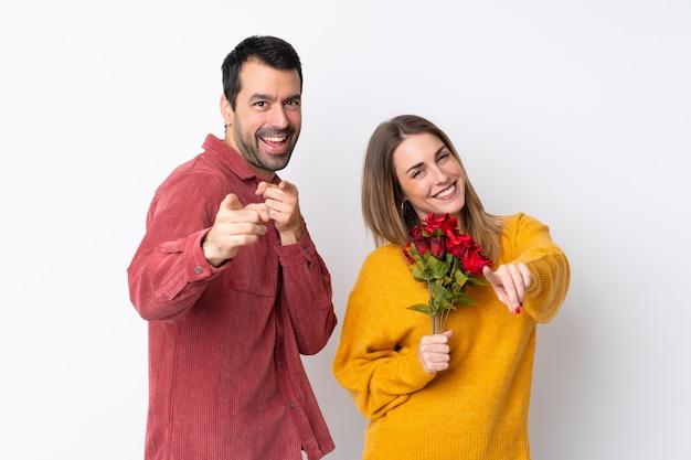 Casal no dia dos namorados, segurando flores sobre parede isolada aponta o dedo para você enquanto sorrindo