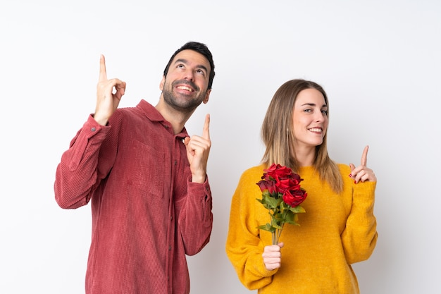 Casal no dia dos namorados segurando flores sobre parede isolada, apontando com o dedo indicador uma ótima idéia