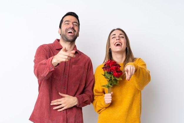 Casal no dia dos namorados, segurando flores sobre parede isolada, apontando com o dedo para alguém e rindo muito