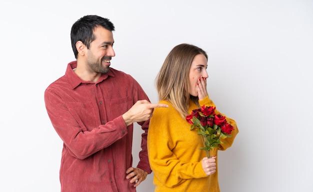 Casal no dia dos namorados, segurando flores sobre parede isolada, apontando o dedo para o lado, com um rosto surpreso
