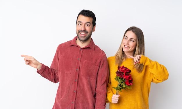 Casal no dia dos namorados, segurando flores sobre parede isolada, apontando o dedo para o lado e apresentando um produto