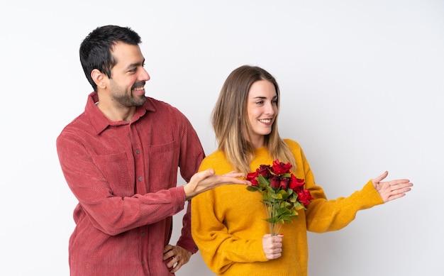 Casal no dia dos namorados, segurando flores sobre parede isolada, apontando para trás e apresentando um produto