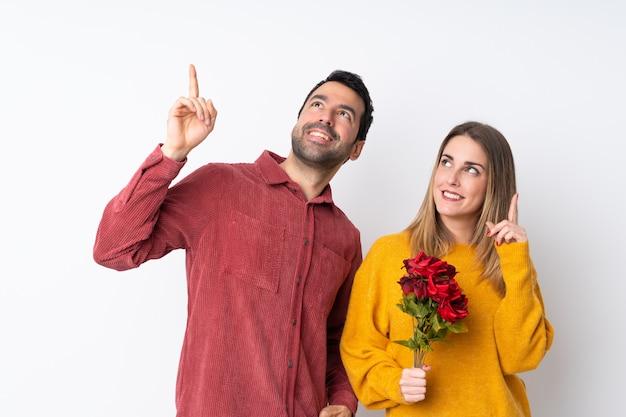 Casal no dia dos namorados, segurando flores sobre parede isolada, apontando uma ótima idéia e olhando para cima