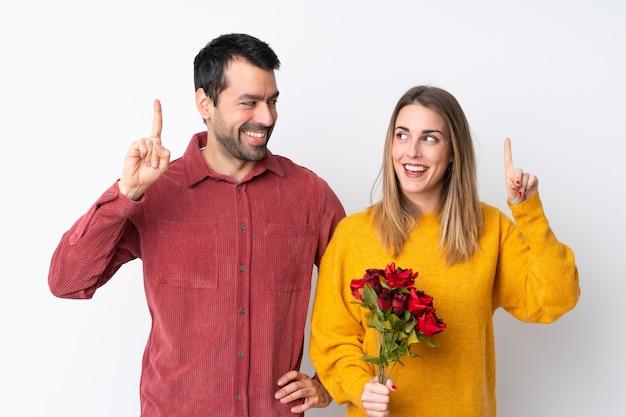 Casal no dia dos namorados segurando flores sobre parede isolada, com a intenção de perceber a solução enquanto levanta um dedo