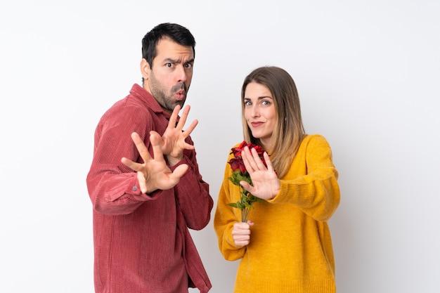 Casal no dia dos namorados segurando flores sobre parede isolada é um pouco nervoso e assustado, esticando as mãos para a frente