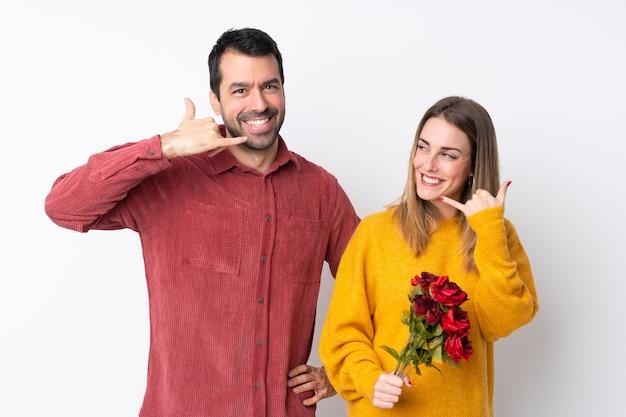 Casal no dia dos namorados, segurando flores sobre parede isolada, fazendo gesto de telefone. ligue para mim de volta