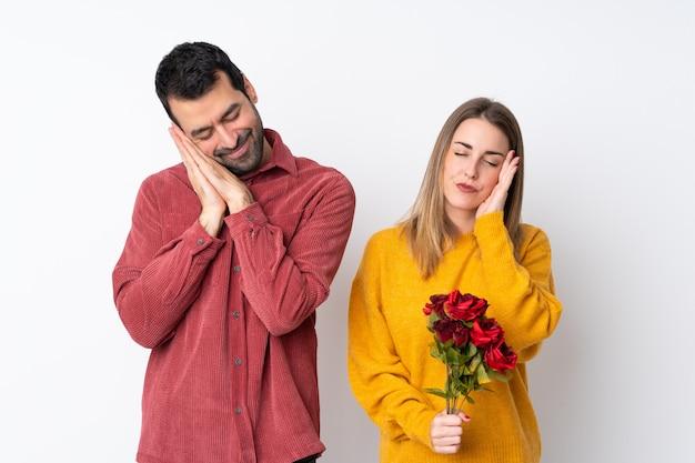Casal no dia dos namorados, segurando flores sobre parede isolada, fazendo o gesto do sono em expressão dorable