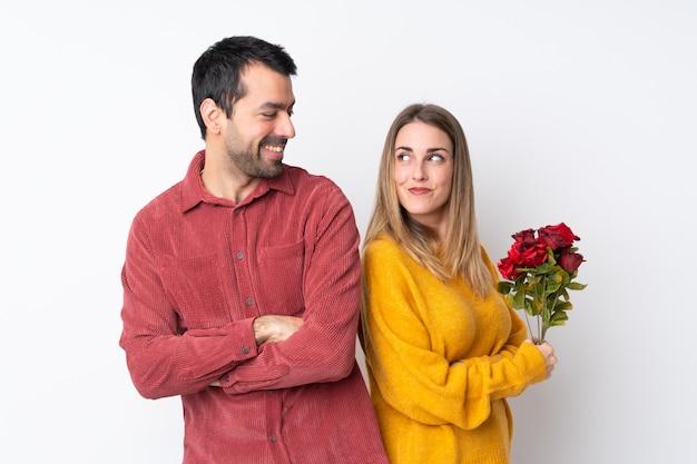 Casal no dia dos namorados segurando flores sobre parede isolada, olhando por cima do ombro com um sorriso
