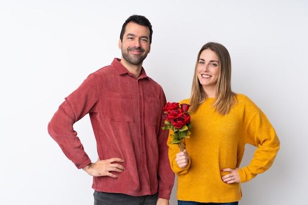 Casal no dia dos namorados, segurando flores sobre parede isolada, posando com os braços no quadril e sorrindo