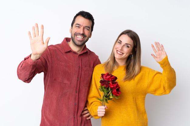 Casal no dia dos namorados, segurando flores sobre parede isolada, saudando com mão com expressão feliz