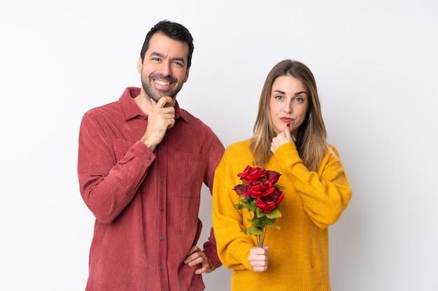 Casal no dia dos namorados segurando flores sobre parede isolada, sorrindo e olhando para a frente com cara confiante