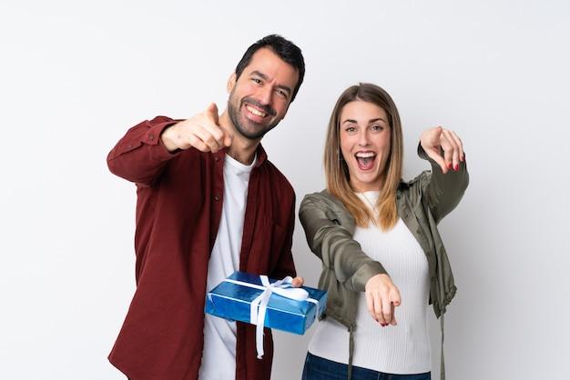 Casal no dia dos namorados, segurando um presente sobre a parede isolada aponta o dedo para você com uma expressão confiante