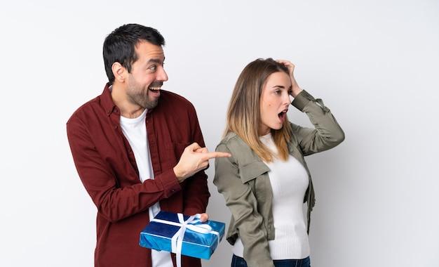 Casal no dia dos namorados, segurando um presente sobre parede isolada, apontando o dedo para o lado, com um rosto surpreso