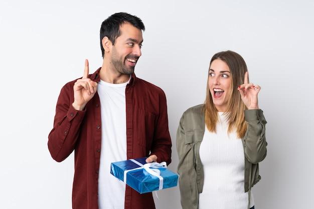Casal no dia dos namorados, segurando um presente sobre parede isolada, com a intenção de perceber a solução enquanto levanta um dedo