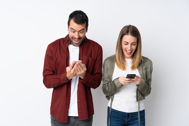 Casal no dia dos namorados sobre parede isolada surpreso e enviando uma mensagem ou e-mail com o celular