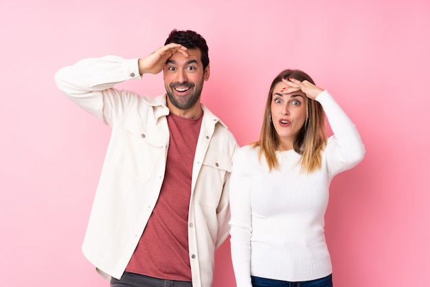 Casal no dia dos namorados sobre parede rosa isolada acaba de perceber algo e tem a intenção de solução