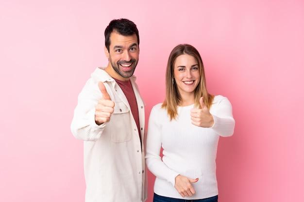 Casal no dia dos namorados sobre parede rosa isolada, dando um polegar para cima gesto, porque algo de bom aconteceu