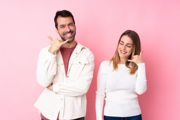 Casal no dia dos namorados sobre parede rosa isolada, fazendo gesto de telefone. ligue para mim de volta