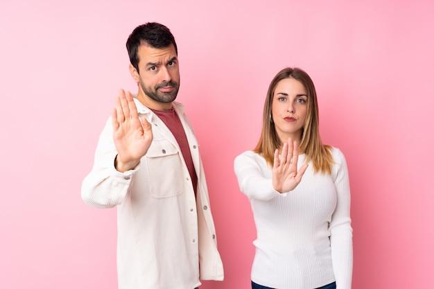 Casal no dia dos namorados sobre parede rosa isolada, fazendo o gesto de parada, negando uma situação que pensa errado